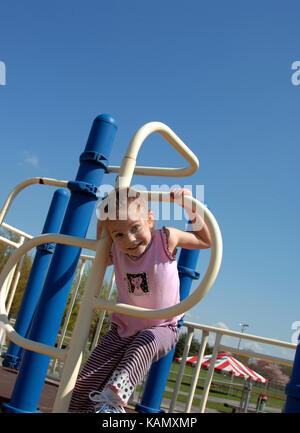 Petite fille grimpe dans un cerceau de métal à l'équipement de jeu. Elle est souriant et heureux. L'équipement est Banque D'Images