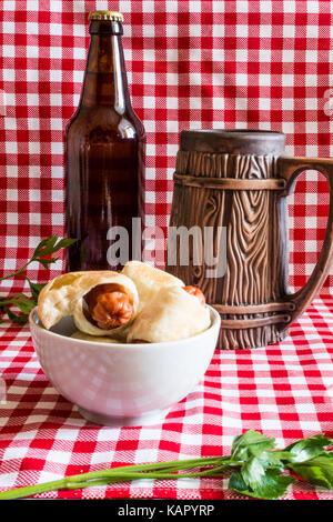 Mini plaque de maison hot dog (saucisse en croûte) sur serviette avec une bouteille de bière brune et faïence mug Banque D'Images