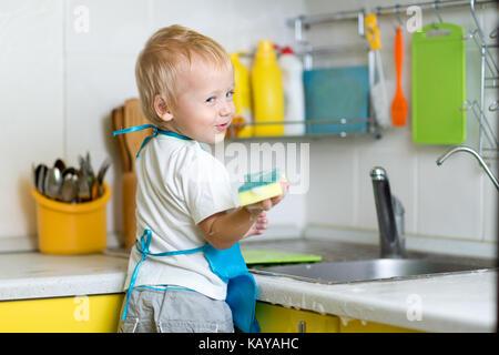 Petit garçon aider mère lave-vaisselle dans la cuisine Banque D'Images