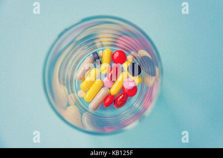 De nombreuses capsules colorées et grillée avec des médicaments dans un petit verre transparent. Le concept de la Banque D'Images