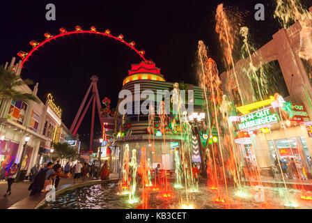 Les touristes et les visiteurs profitent de la marche de nuit autour du centre commercial Shoppes et magasins à Banque D'Images