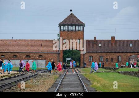 Les touristes de passage en face de la porte d'entrée de l'Auschwitz II Birkenau camp de concentration nazi de la Banque D'Images