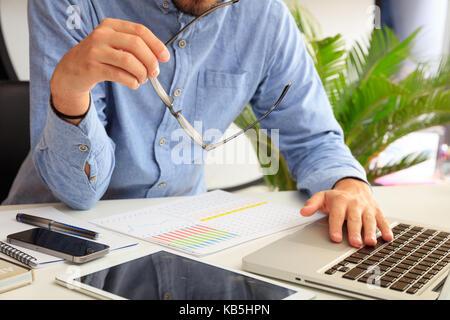 L'homme l'étude d'un rapport d'analyse dans un contexte de bureau Banque D'Images
