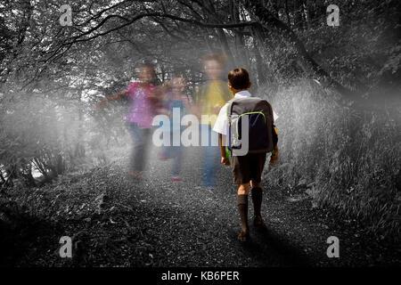 Mignon à l'école marche de l'élève contre bus façon sombre dans les bois Banque D'Images