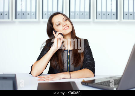 Portrait of young smiling business woman sitting at Office 24 et talking on cell phone Banque D'Images