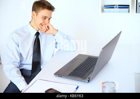 Portrait of young laughing man l'écran de l'ordinateur portable sur son lieu de travail à bright office Banque D'Images