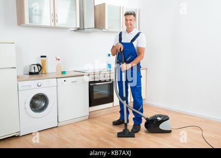 Portrait d'homme janitor cleaning aspirateur dans la cuisine Banque D'Images