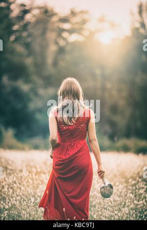 Fille qui marche dans un champ au coucher du soleil, dans une robe rouge, un holdinh miroir argent Banque D'Images