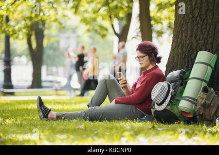 Sac à dos fille adolescente avec tourisme looking at smartphone in city park Banque D'Images