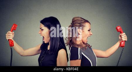 Communication concept. Deux femmes en colère crier par d'autres au téléphone isolé sur fond gris. Banque D'Images