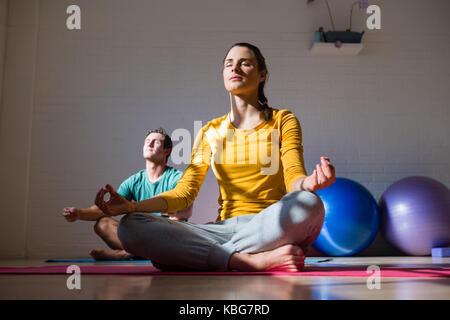 Personnes méditant assis sur tapis d'exercice au club de santé Banque D'Images