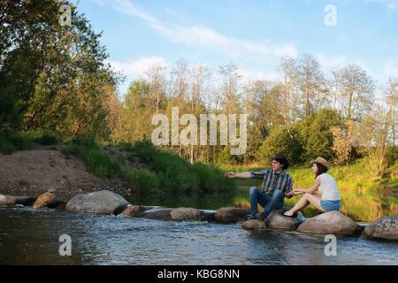 Couple de jeunes gens admirer le coucher de soleil dans la soirée de printemps o Banque D'Images
