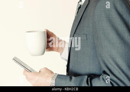 Homme sans tête profil professionnel vue latérale à l'aide de smart mobile phone tout en tenant une tasse de café en poste à l'horizontale. Banque D'Images