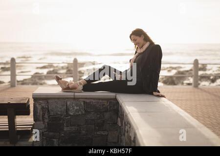 Femme enceinte assis près de la plage sur une journée ensoleillée Banque D'Images