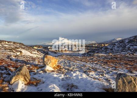 La lumière du jour vue d'un lointain maisons de banlieue de la ville de Nuuk, avec en toile de fond la montagne Banque D'Images