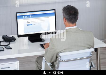 Vue arrière du businessman en signature website at desk in office