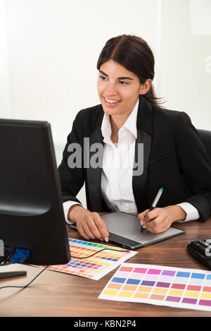 Femme concepteur à l'aide de tablette graphique avec l'échantillon de couleur à 24 Banque D'Images