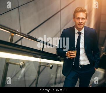 Smiling young businessman en costume de boire un café et de remonter un escalator dans une station de métro au cours de son trajet du matin