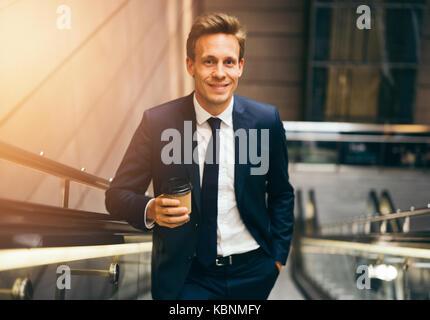 Confident young businessman smiling en buvant un café et d'un escalator dans une station de métro au cours de son trajet du matin
