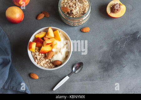 L'avoine fait maison avec du yogourt et granola pêches au bol pour petit-déjeuner sain. des céréales et des fruits Banque D'Images