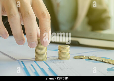 L'argent, financier, la croissance de l'entreprise concept, la main de l'homme d'affaires mettre de l'argent monnaie Banque D'Images