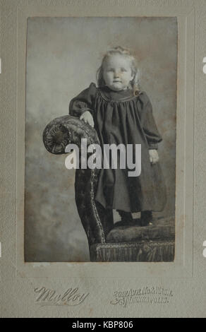 Archive américaine studio monochrome portrait photographique de jeunes enfant debout sur une chaise longue canapé, Banque D'Images