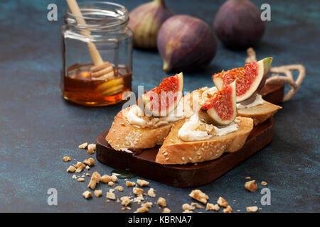 Des sandwichs aux figues, ricotta, miel, noix, figues fraîches et un pot de miel sur un fond bleu Banque D'Images
