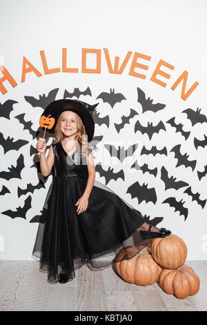 Smiling little girl habillé en costume halloween tenant un masque tout en se posant avec des citrouilles et des Banque D'Images