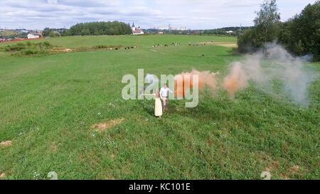Relevé aérien de couple marche sur le terrain avec la fumée de couleur dans les mains. voler au-dessus de l'homme Banque D'Images
