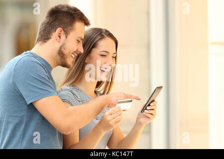 Couple heureux de vos achats en ligne avec un téléphone intelligent et une carte de crédit en face d'une boutique Banque D'Images