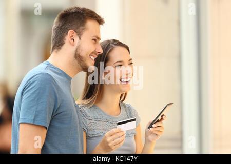 Couple de vos achats en ligne avec une carte de crédit et un téléphone intelligent regarder une vitrine de l'extérieur, Banque D'Images