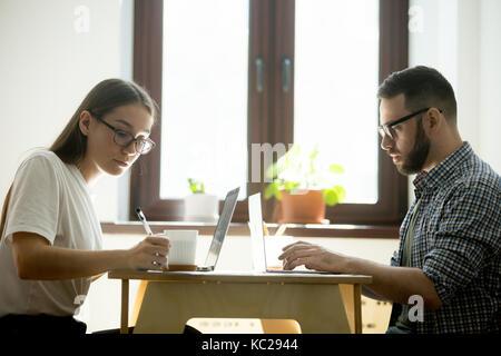 L'homme et la femme travaillant sur des ordinateurs portables dans un café, en prenant des notes. Le travail à distance, offres de concept.