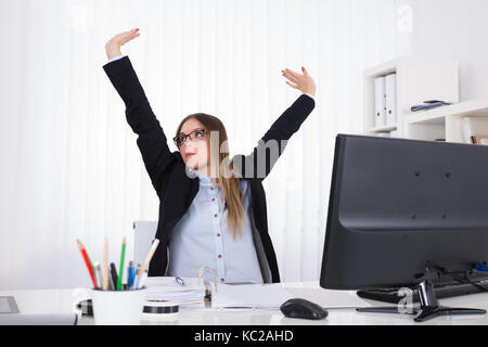 Young Woman stretching her arms in office Banque D'Images