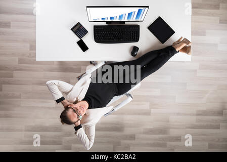 High angle view of happy businesswoman relaxing on chair in office Banque D'Images