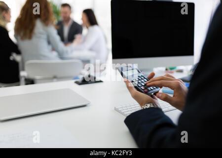 L'analyse des diagrammes de l'investissement d'affaires avec la calculatrice sur office 24 Banque D'Images