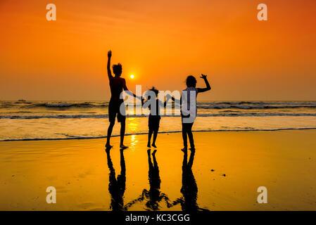 Silhouettes d'un groupe d'enfants danser sur la plage au coucher du soleil. Banque D'Images
