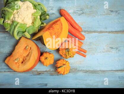 Pumpkin muscat, simple et décorative, les carottes et les choux-fleurs sur un fond de bois bleu rustique. la saine Banque D'Images