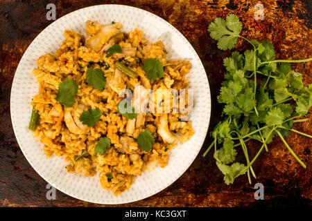 Nasi Goreng au poulet nourriture indonésienne contre un four en détresse ou de cuisson avec une bande d'herbes coriandre Banque D'Images