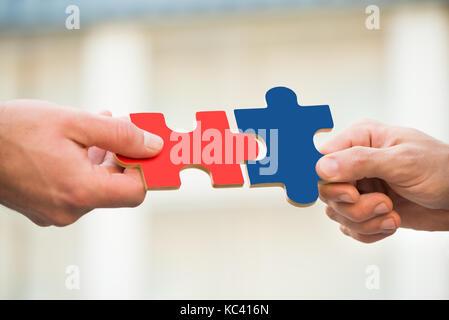 Mains coupées d'hommes d'affaires de se joindre à l'extérieur des pièces de puzzle Banque D'Images