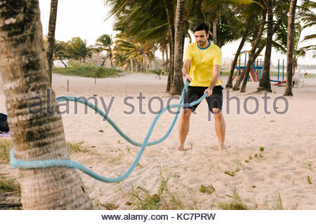 Jeune homme athlétique avec corde de formation sur la plage Banque D'Images