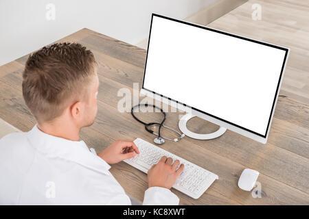 Jeune homme médecin à l'aide d'ordinateur sur 24 en clinique Banque D'Images