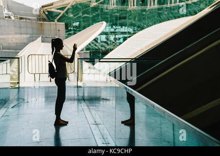 Silhouette contre la lumière de la jeune femme à prendre des photos dans un immeuble moderne Banque D'Images