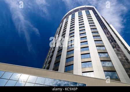 La perspective et l'angle de vue de dessous de verre fond texturé moderne bâtiment gratte-ciel sur blue cloudy sky Banque D'Images