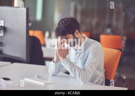 Jeune homme d'affaires travaillant sur ordinateur de bureau à son bureau au démarrage lumineux moderne office interior Banque D'Images