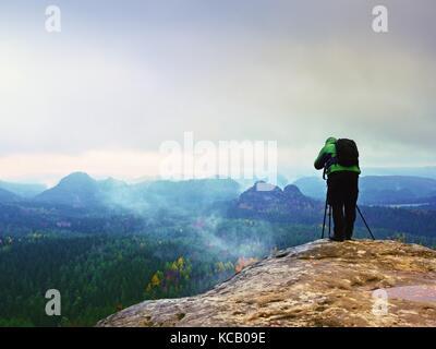 Photographe professionnel en veste verte avec sac à dos prend des photos avec l'appareil photo sur trépied sur piton Banque D'Images