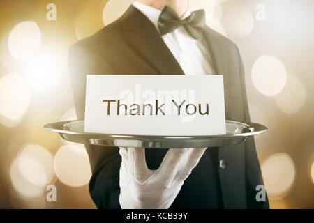 Close-up of a waiter holding carte de remerciement dans le bac