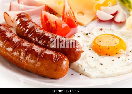 Petit déjeuner - œuf frit et saucisses, fromage, jambon et légumes Banque D'Images