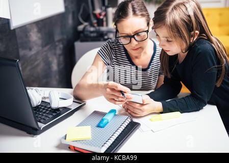 Mère et fille à l'aide de smart phone at home office Banque D'Images