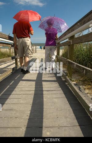 Senior couple holding parasols tout en marchant à Myrtle Beach SC, USA. Banque D'Images