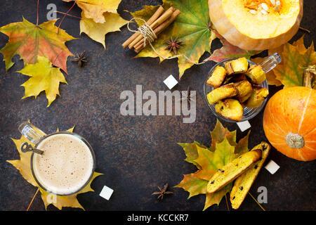 Des raisins et cannelle biscuits et une tasse de cappuccino sur une table en bois de cuisine. Banque D'Images